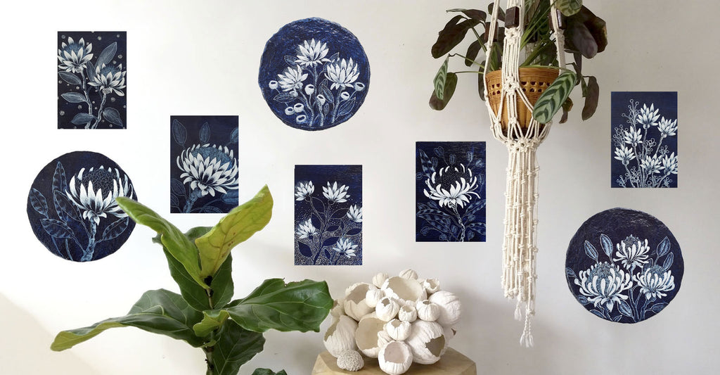 Gallery wall jungalow style vignette displaying one of a kind original paper porthole artworks featuring blue and white designs of Australian Native flowers. All artworks including paper barnacle sculpture created by Australian artist Rebecca Coulter