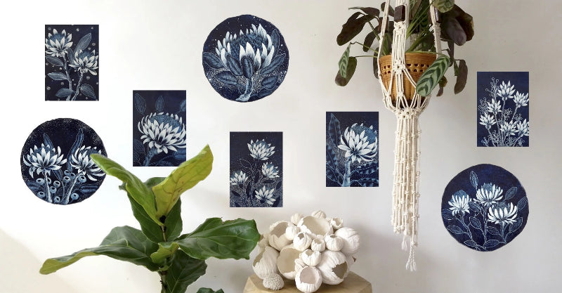 Gallery wall jungalow style vignette displaying one of a kind original wooden block and paper porthole artworks featuring blue and white designs of Australian wildflowers. Created by Australian artist Rebecca Coulter