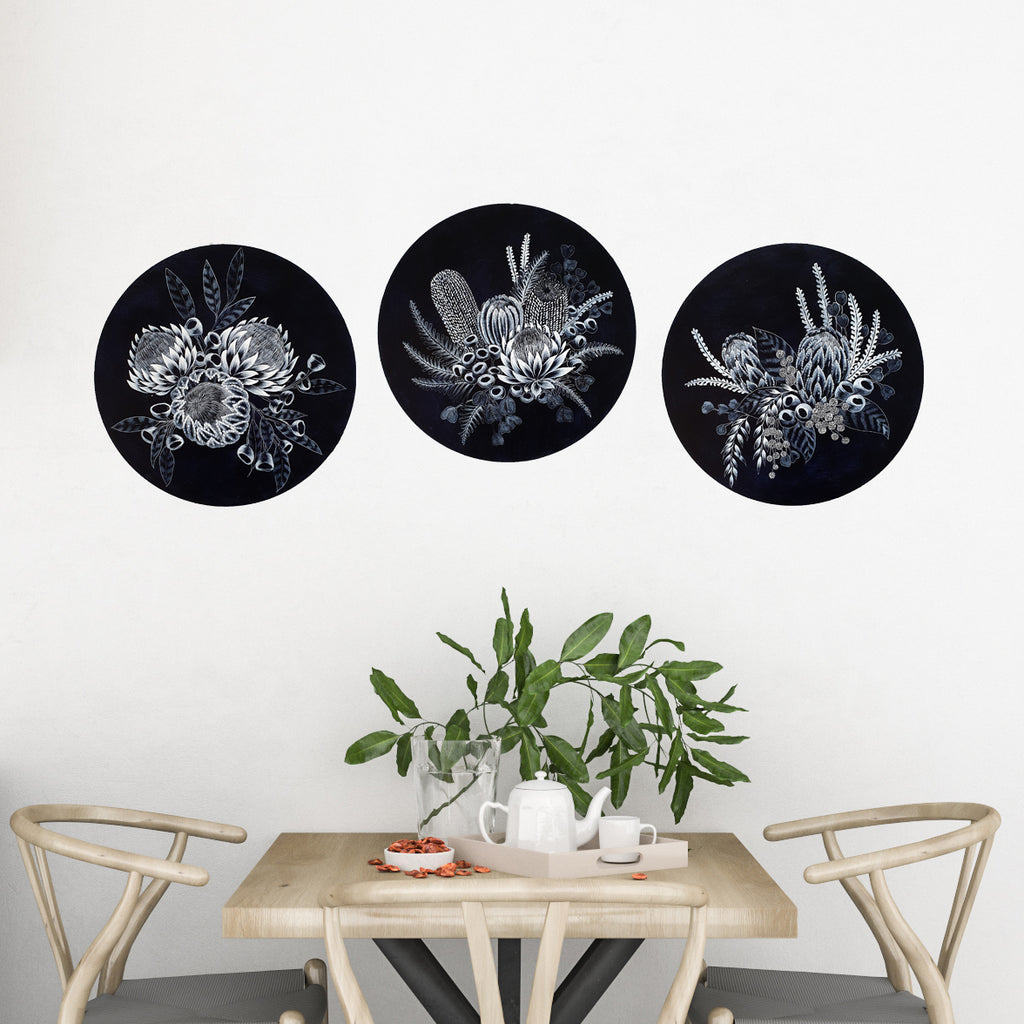 Three blue and white circular porthole paintings featuring Proteas, waratahs and other native Australian wildflowers. Displayed on a wall above a contemporary sunlit timber dining setting. Original Australian art created by ArtistaStyle