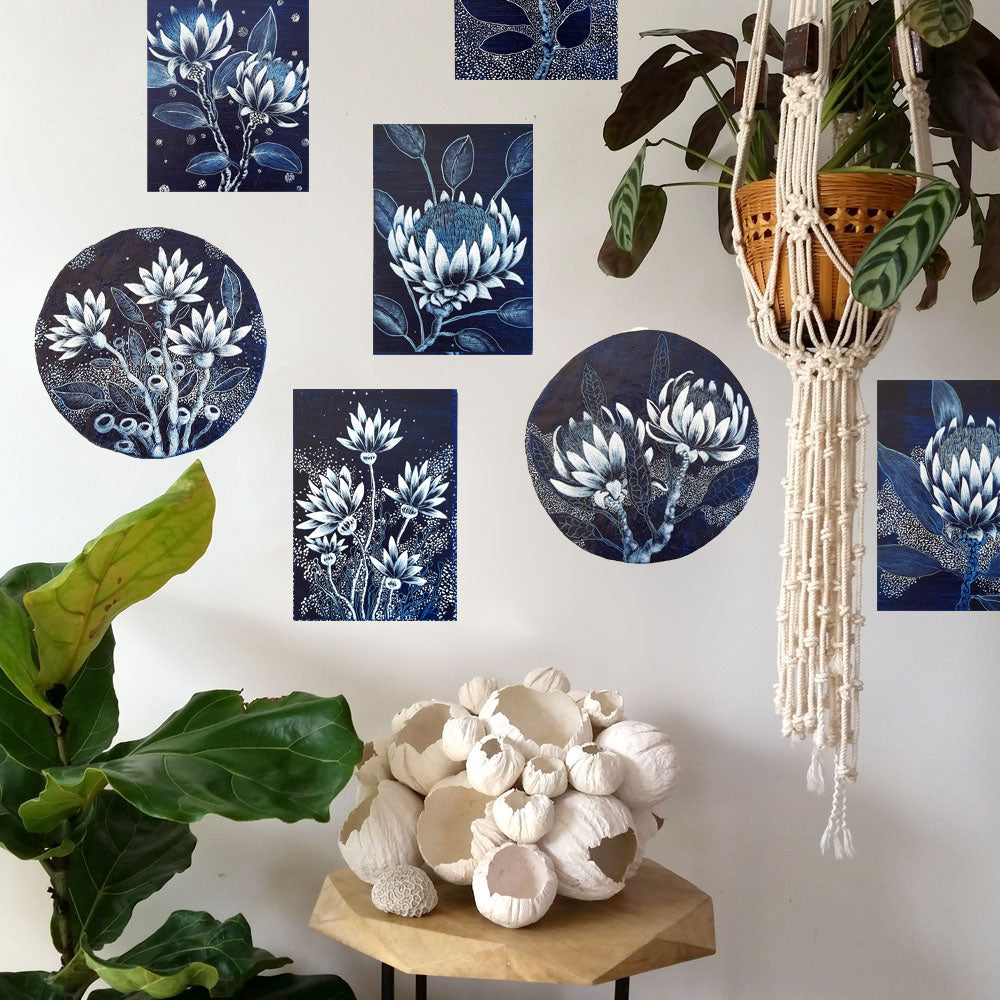 Gallery wall jungalow style vignette displaying one of a kind original wooden block and paper porthole artworks featuring blue and white designs of Australian wildflowers. All artworks including paper barnacle sculpture created by Australian artist Rebecca Coulter