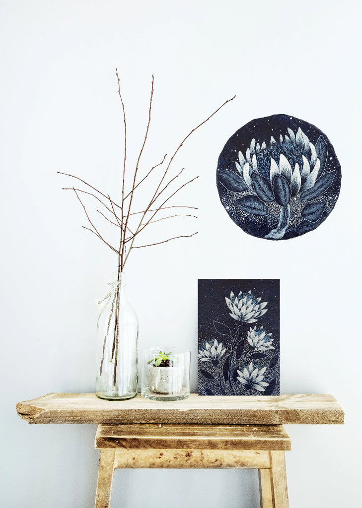 An original blue and white paper porthole painting of a Protea displayed on a wall with a tabletop vignette featuring a contemporary wooden stool with a blue and white floral design woodblock resting on its surface. Original one of a kind artworks created by Rebecca Coulter