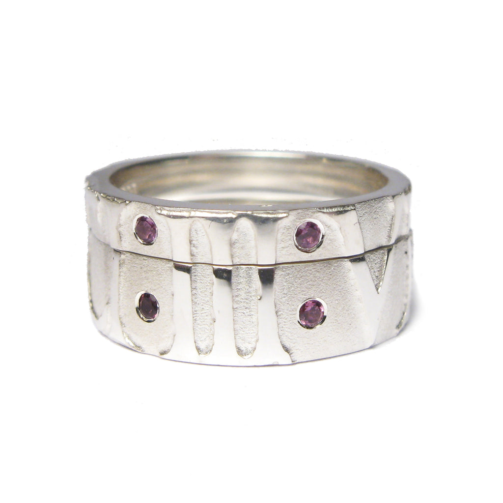 Diana Porter Contemporary jewellery Bespoke silver partnership rings with relief etching and garnets.