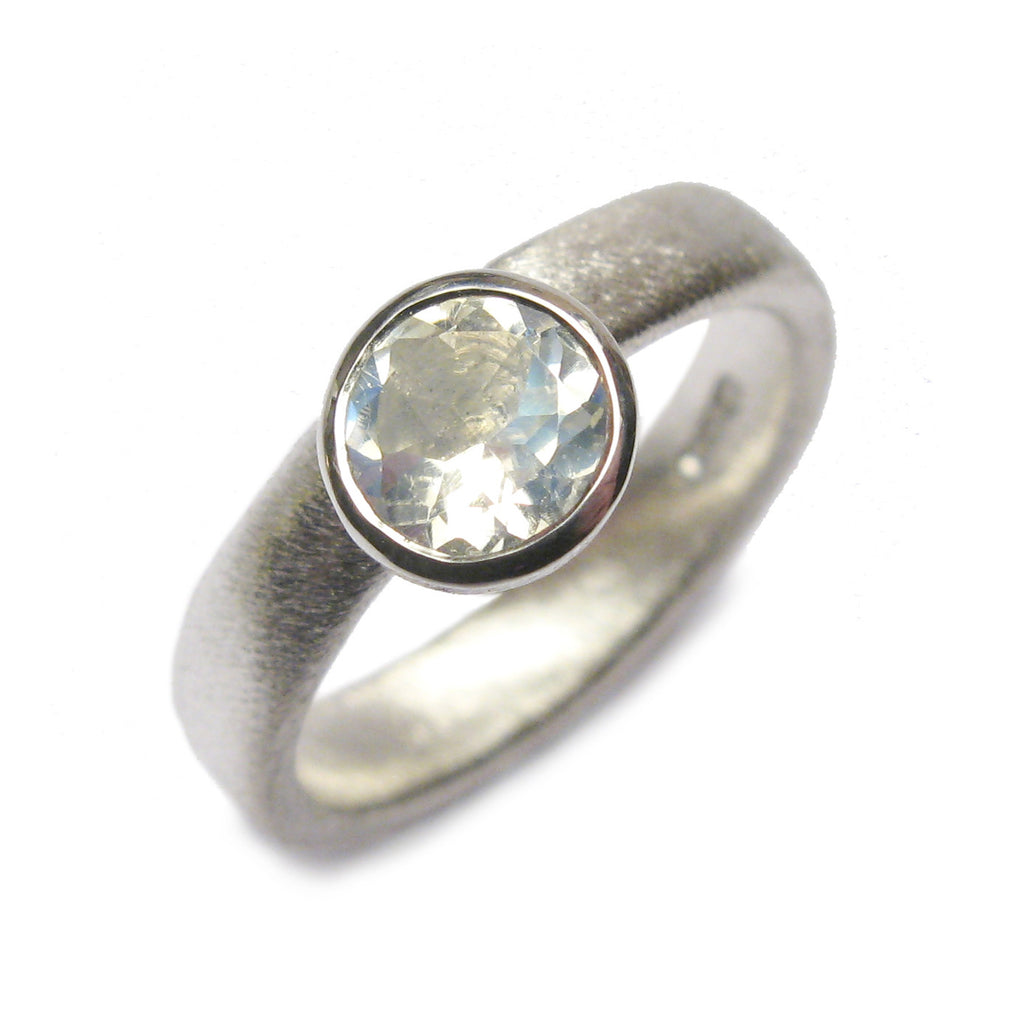 Bespoke silver ring set with a large, faceted moonstone.