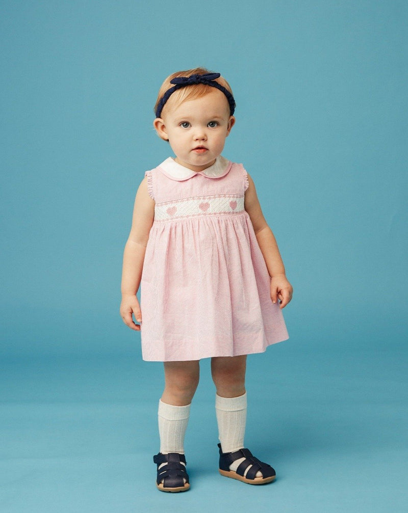 baby wearing pink hand-smocked dress