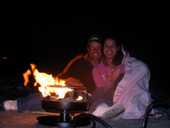 couple under blanket with campfire in a can burning in foreground