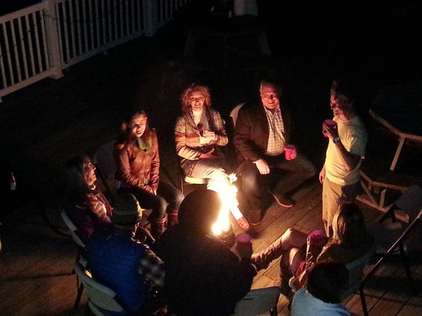group sitting around campfire in a can