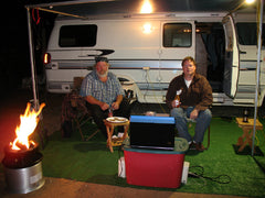 2 men sitting in chairs next to rv camper with campfire in a can burning