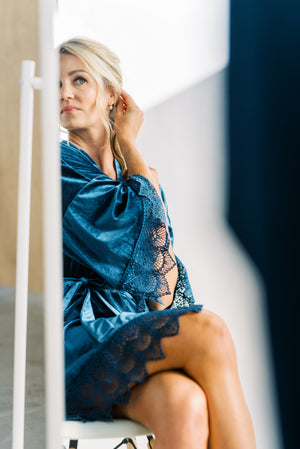Bride getting ready for her wedding day in a dusty blue velvet robe