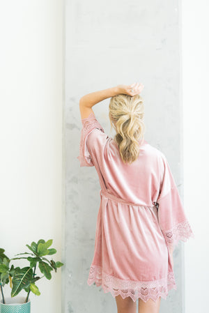Bride wearing a rose pink velvet and lace robe