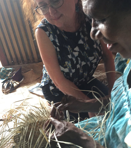 Rosie watching Rachael weave a pandanus straw hat in Vanuatu