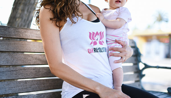 Sarah Clark wearing an OM Revolution tank holding her baby