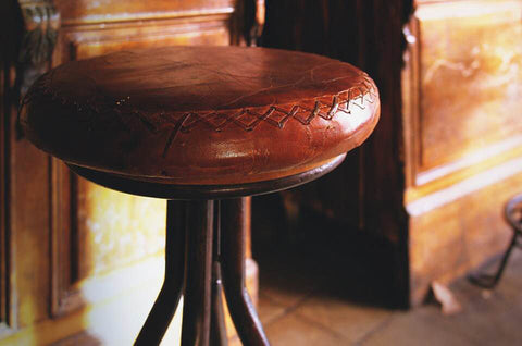 A beautiful distressed leather stool. If you spill your drink on it, blot away the moisture instead of rubbing.