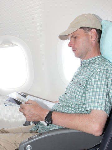 A man gets comfortable with his pillowpacker pillow on board a flight