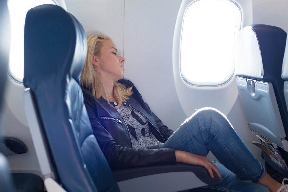 woman sore trying to sleep in flight