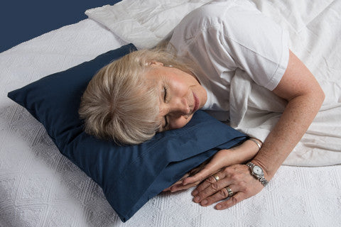 A woman comfortably rests on a pillowpacker pillow
