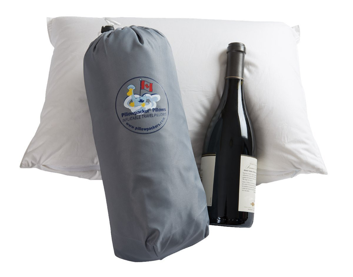 A Pillowpacker Hutterite goose down pillow and protective case pictured with a bottle of wine