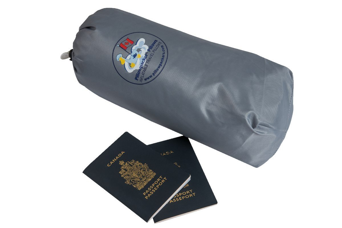 A Pillowpacker goose down alternative pillow in its protective carrying case next to two passports