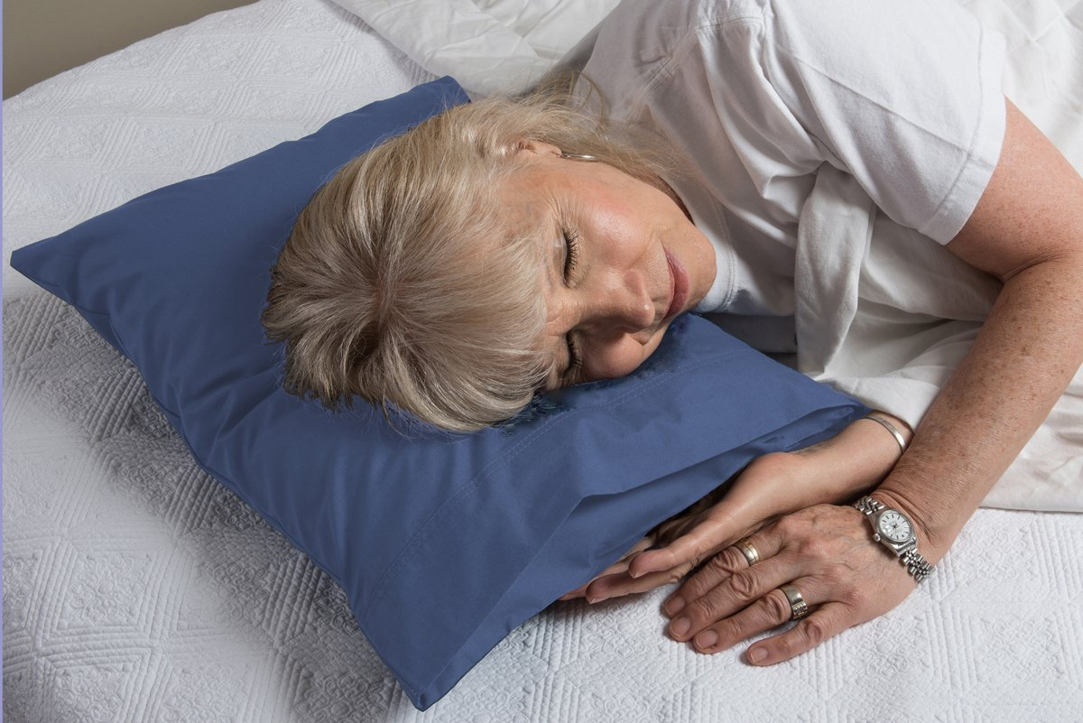 A woman lays down on a Pillowpacker White down blend pillow