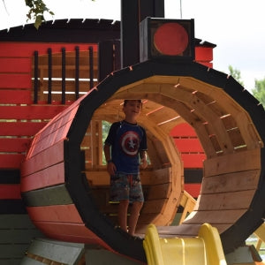 child playing inside a wooden train playhouse