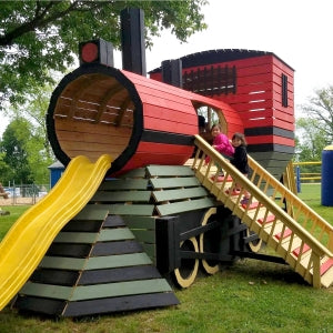 kids climbing into wooden train playhouse