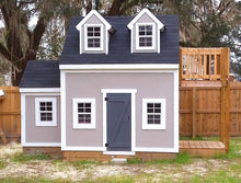 A grey painted playhouse with balcony, dormers and trim