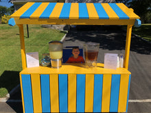 Blue and yellow lemonade stand with a boy and drinks