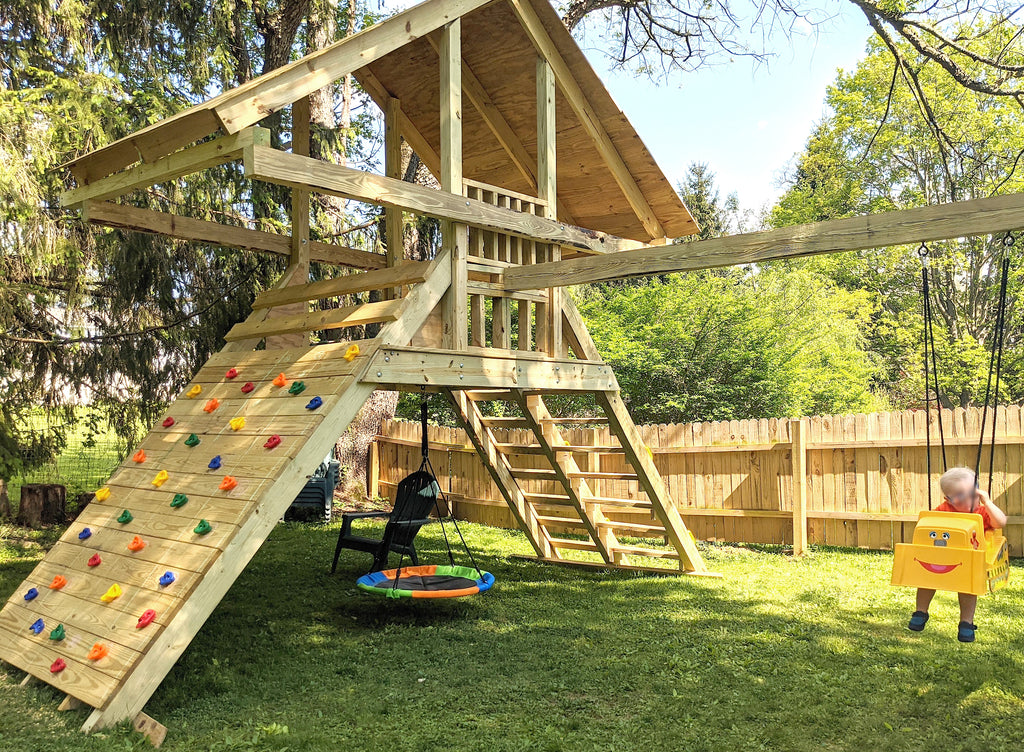 Backyard A-frame playset with rock wall