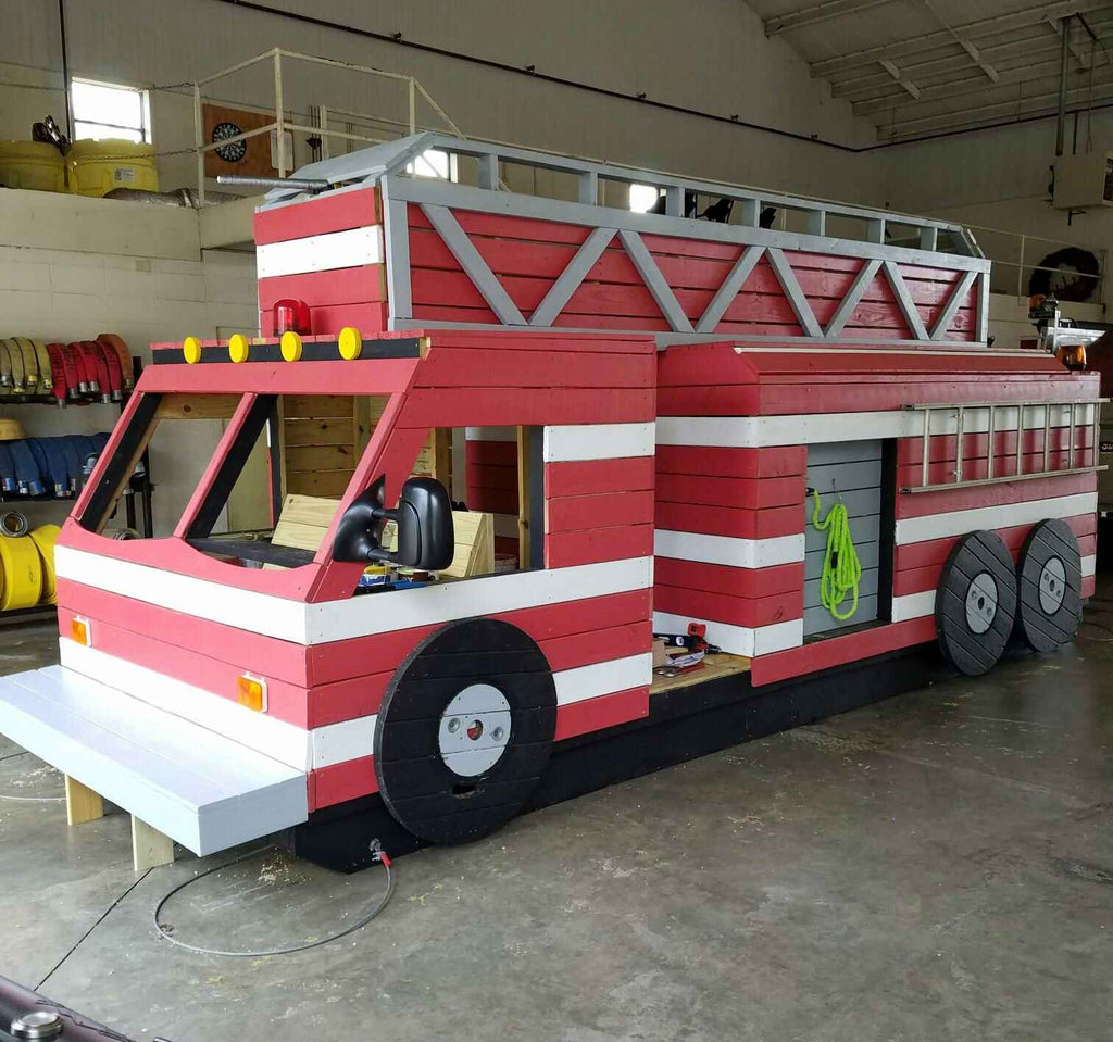 Red fire truck playset inside a firehouse