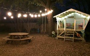 Cozy open, elevated playhouse with lights at night