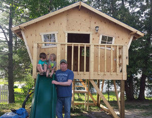 father and sons outside wooden playhouse plan