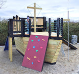boy playing on a playground pirate ship with slide, gang plank and rock wall.