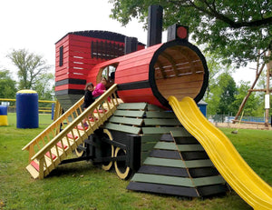 two girls climbing on large wooden train playhouse