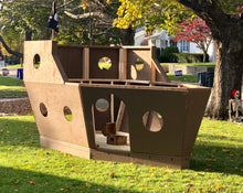 A small, wooden pirate ship in a front yard