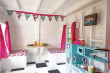 Inside the camper playhouse with a table, chairs and kitchen-set