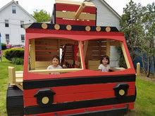 girls playing inside wooden firetruck playhouse