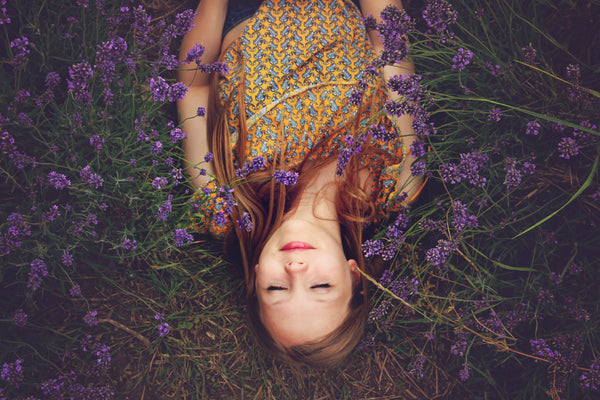 pretty girl relaxed and smiling, laying on a bed of grass and lavender flowers