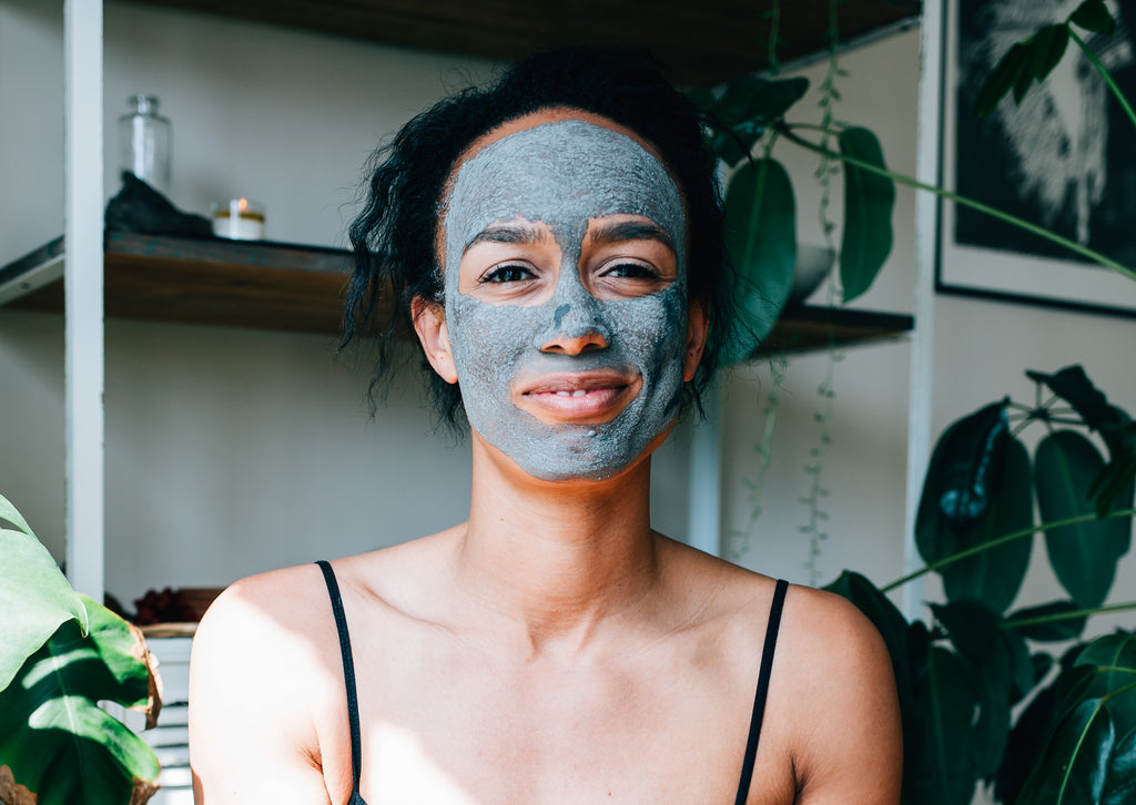 Young woman smiling at camera while wearing the Activated Purifying Mask made from French green clay by natural skincare brand, Apoterra Skincare.