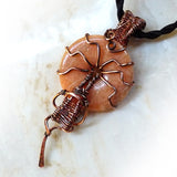 Peach gemstone donut is wire wrapped in copper wire