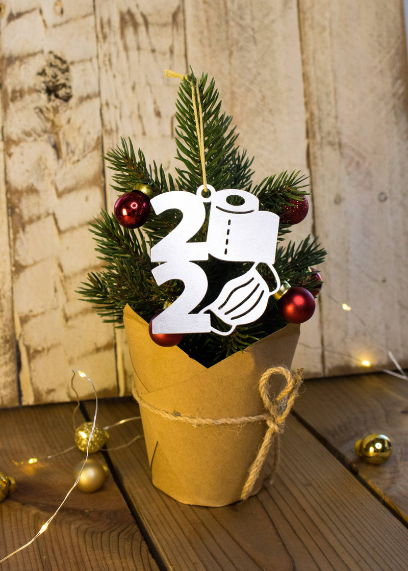 Aluminum 2020 Christmas Ornament hanging on miniature tree ornament features a roll of toilet paper and mask instead of zeros