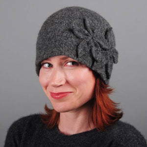 Model of a handmade dark grey wool hat with two wool flowers sewn on. Handmade by Julie Sinden Handmade.