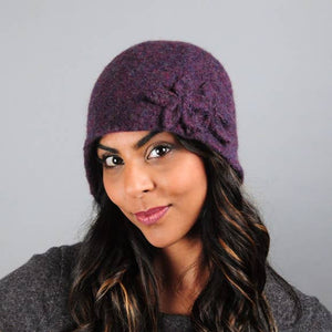 Model of a handmade purple wool hat with two wool flowers sewn on. Handmade by Julie Sinden Handmade.
