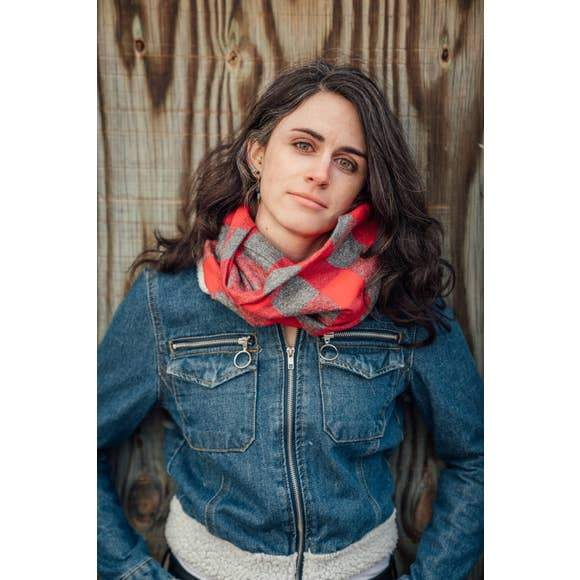 Model wearing a red and grey buffalo plaid infinity scarf handmade by Nicole's Threads.
