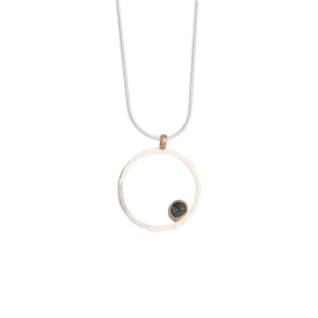 "Mini .75"" in Diameter Hollow Sterling Silver Circle Pendant with an off center 14k rose gold bezel for a grey rough diamond shard, rose gold bale and sterling silver chain on with background"