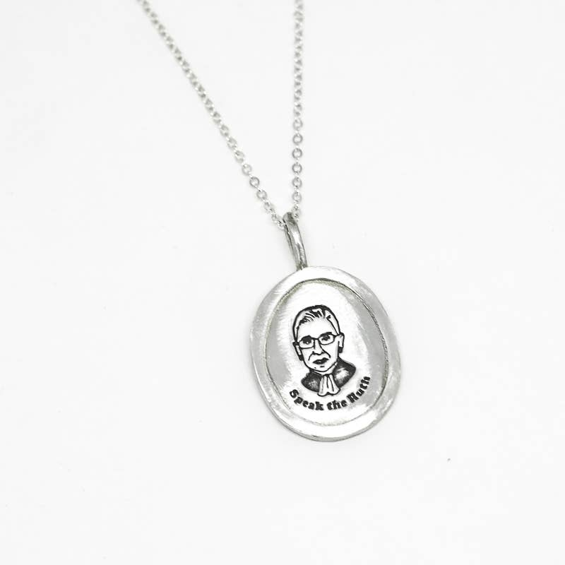 "Silver Pendant with a picture of RBG and read ""speak the ruth"""