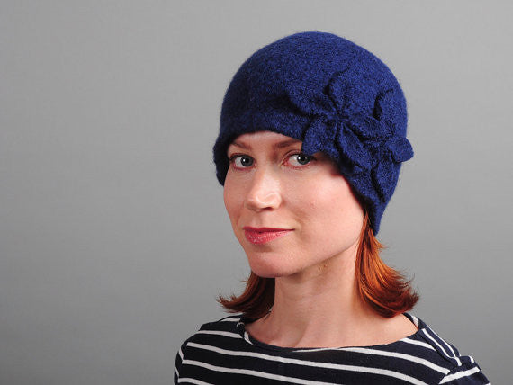 Model of a handmade navy blue wool hat with two wool flowers sewn on. Handmade by Julie Sinden Handmade.