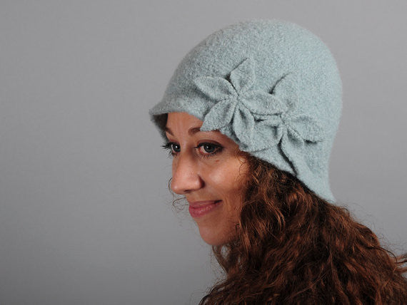 Model of a handmade seafoam green wool hat with two wool flowers sewn on. Handmade by Julie Sinden Handmade.