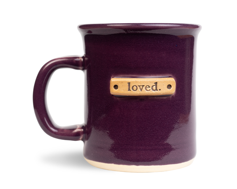 loved stamped on a plum colored ceramic mug