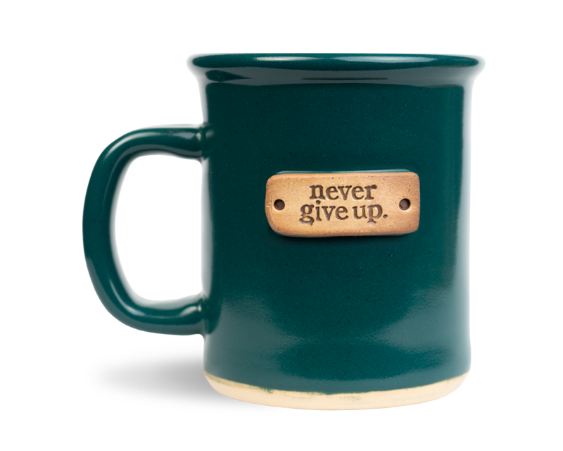 never give up stamped on a jade colored 12oz mug