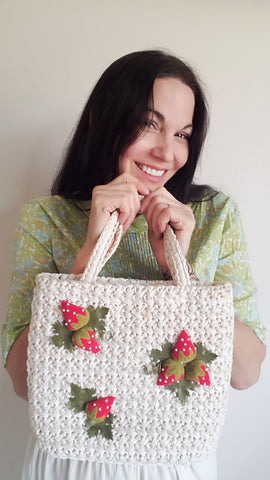 Smiling woman wearing vintage blouse and holding a vintage purse
