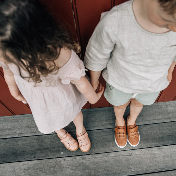 toddler boy and girl holding hands wearing matching shoes
